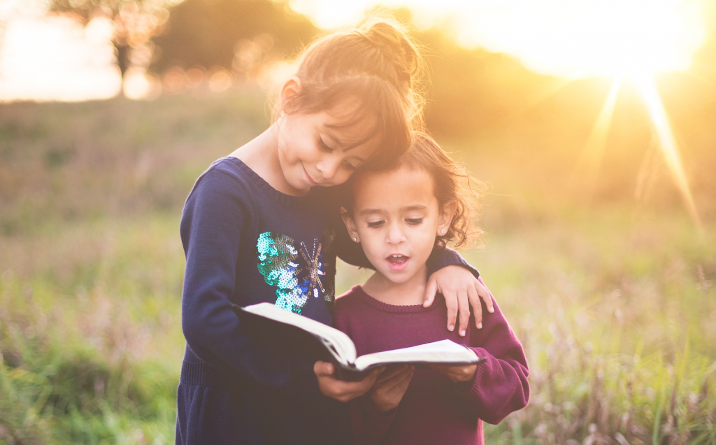 an elementary school aged girl and preschool aged girl embracing while reading a book
