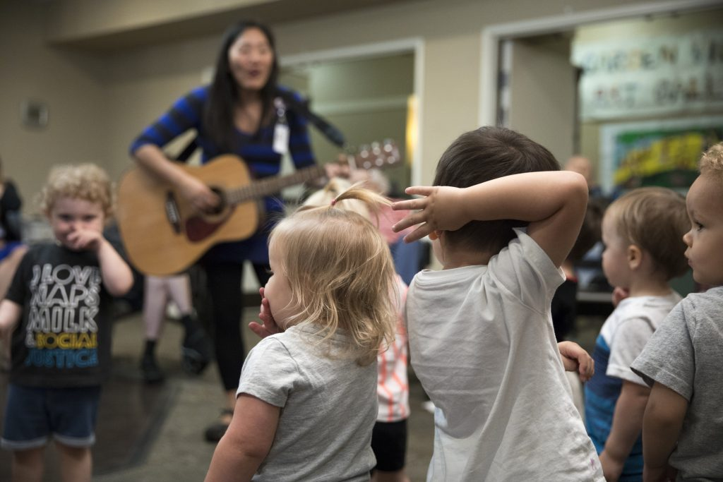 a teacher sings and plays guitar to a group of toddlers